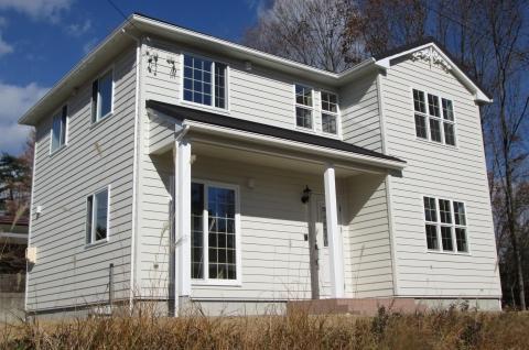 青色の空と白色の外壁のコントラストが美しい家